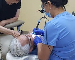 Dr. Wang treating patient in dental chair