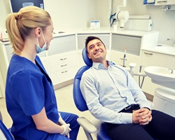 man in blue shirt sitting in dental chair