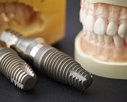 False teeth and dental implant on table