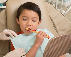 Child brushing teeth in dental chair