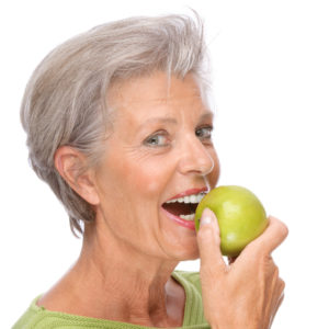 older woman holding green apple